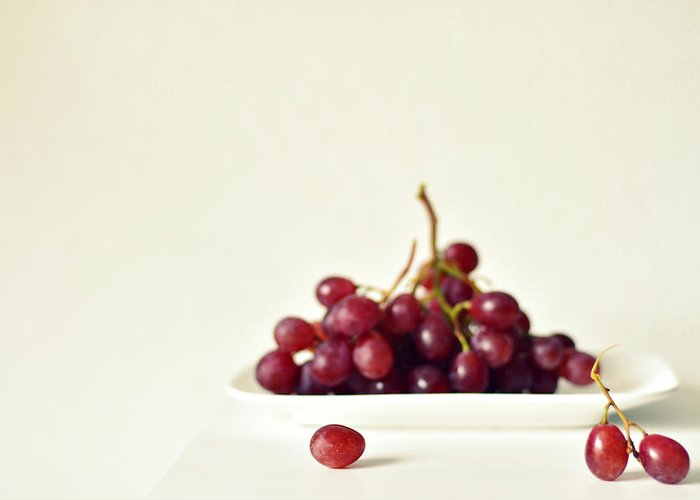White Background Greeting Card featuring the photograph Red Grapes On White Plate by Photo By Ira Heuvelman-dobrolyubova