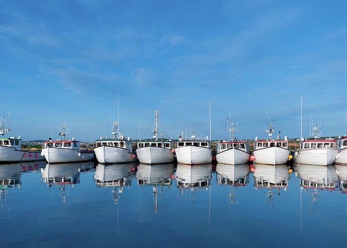 Iles De La Madeleine Greeting Card featuring the photograph Row Of Boats With Reflection by Pndtphoto