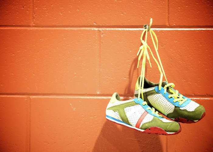 Hanging Greeting Card featuring the photograph Runnig Shoes Hanging On A Hook by Pascalgenest