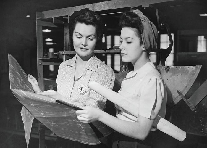 Plan Greeting Card featuring the photograph Two Women In Workshop Looking At by George Marks
