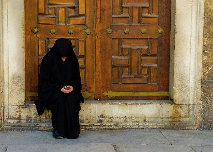 Istanbul Greeting Card featuring the photograph Veiled Girl Send Message On Mobile Phone by Marco Vacca