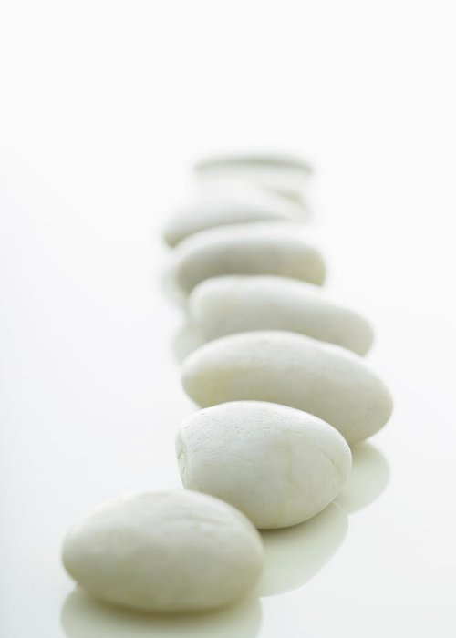 White Background Greeting Card featuring the photograph White Stones Lined Up On A White by Rick Lew