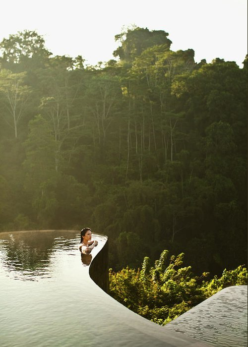 Tropical Rainforest Greeting Card featuring the photograph Woman In Infinity Pool At Sunrise. Bali by Matthew Wakem