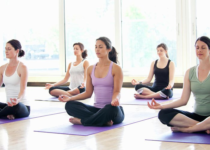 Mid Adult Women Greeting Card featuring the photograph Women Practicing Yoga In A Class by Assembly