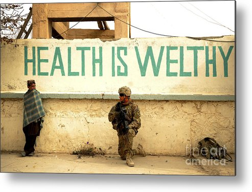 Village Metal Print featuring the photograph A Soldier Talks To An Afghan Boy by Stocktrek Images