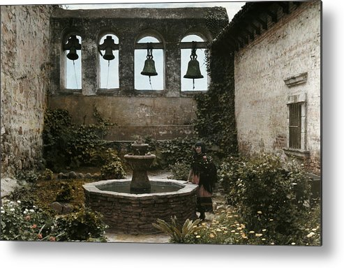 Day Metal Print featuring the photograph A Woman Stands Next To A Fountain by Charles Martin
