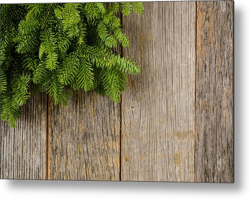 Green Metal Print featuring the photograph Tree Branch On Rustic Wooden Background Used For Christmas Decor by Brandon Bourdages
