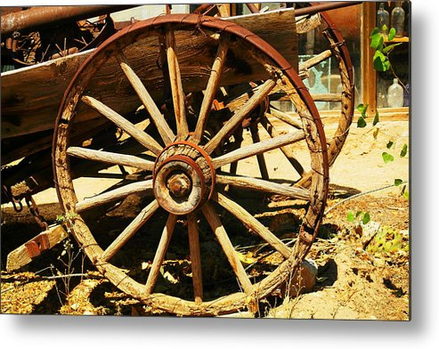 Rounds Metal Print featuring the photograph A Wagon Wheel by Jeff Swan