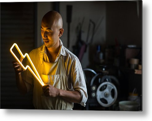 Working Metal Print featuring the photograph Craftsmen Holding A Lightning Bolt Shaped Neon Light by Trevor Williams