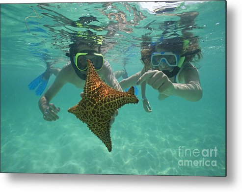 People Metal Print featuring the photograph Snorkellers Holding A Four Legs Starfish by Sami Sarkis