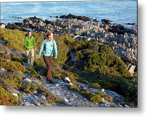 Adventure Metal Print featuring the photograph Two Women Hiking On An Ocean Trail by Lars Schneider