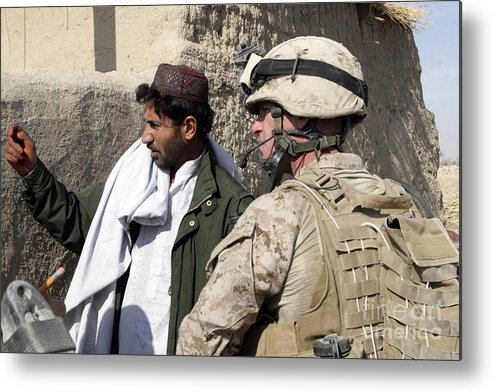 Marines Metal Print featuring the photograph A Soldier Talks To A Local Villager by Stocktrek Images