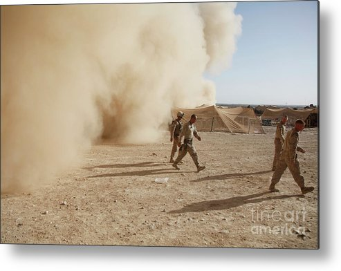 Debris Metal Print featuring the photograph U.s. Marines Walk Away From A Dust by Stocktrek Images