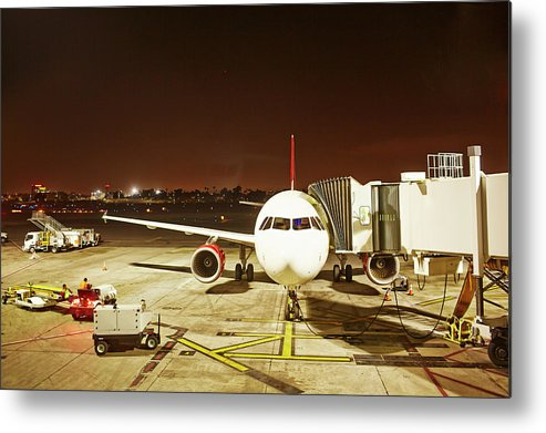 Passenger Boarding Bridge Metal Print featuring the photograph Airplane Parked At Jetway by Ballyscanlon