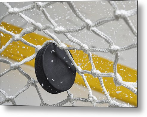 Goal Metal Print featuring the photograph Close-up of an Ice Hockey puck hitting the back of the net as snow flies, front view by Cmannphoto
