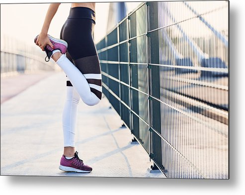 Recreational Pursuit Metal Print featuring the photograph Close-up of woman stretching legs after running by Westend61