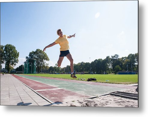 North Holland Metal Print featuring the photograph Senior Athlete (75) Practicing Long Jump by Lucy Lambriex
