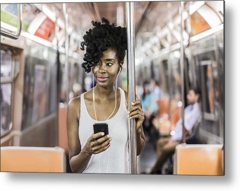 Mid Adult Women Metal Print featuring the photograph USA, New York City, Manhattan, portrait of relaxed woman with cell phone in underground train by Westend61