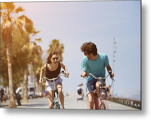 Young Men Metal Print featuring the photograph Woman chasing man while riding bicycle by Morsa Images