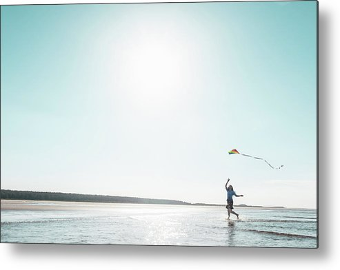 Three Quarter Length Metal Print featuring the photograph Woman Flying Kite On Beach by Dan Brownsword