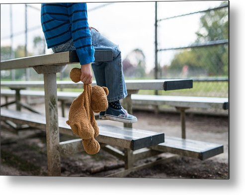 Empty Metal Print featuring the photograph Young boy sitting by himself on on bleachers. by FatCamera
