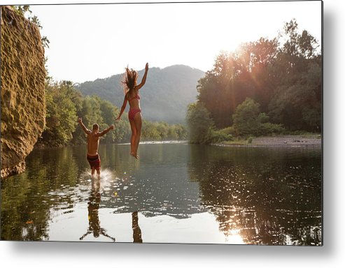 Young Men Metal Print featuring the photograph Young Couple Jumping Into River by Zave Smith