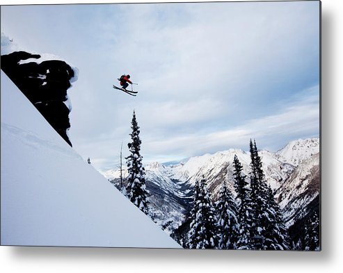 Skiing Metal Print featuring the photograph A Athletic Skier Jumping Off A Cliff In by Patrick Orton