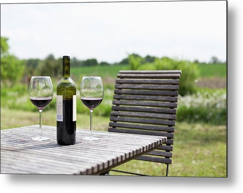 Five Objects Metal Print featuring the photograph Glasses And A Bottle Of Red Wine On An by Halfdark