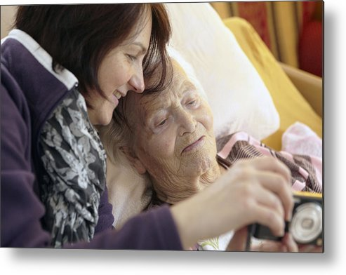 Mature Adult Metal Print featuring the photograph Bedridden Grandmother With Granddaughter by Martin Leigh