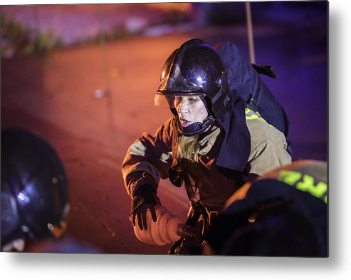 Working Metal Print featuring the photograph Female firefighter helping injured by Vm