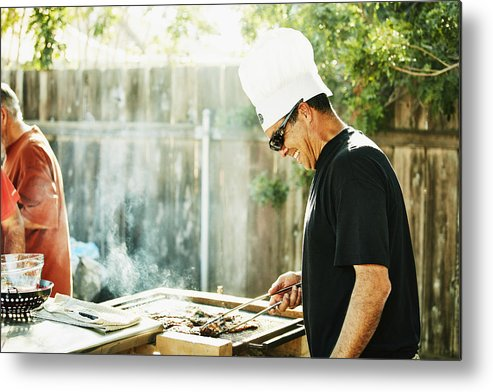 Expertise Metal Print featuring the photograph Smiling father grilling in backyard during family barbecue by Thomas Barwick