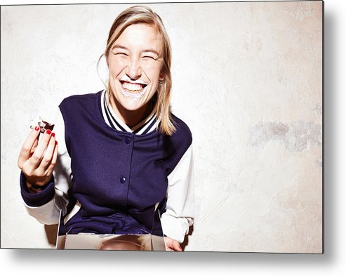Unhealthy Eating Metal Print featuring the photograph Studio shot of young woman eating chocolate marshmallows by Conny Marshaus