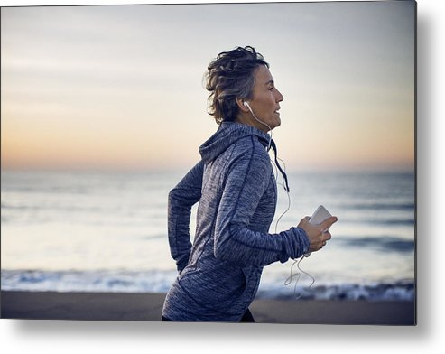 Tranquility Metal Print featuring the photograph Woman jogging while listening music at beach against sky by Cavan Images