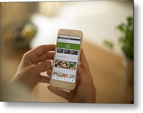 Internet Metal Print featuring the photograph Woman using meal delivery service through mobile app. by Svetikd