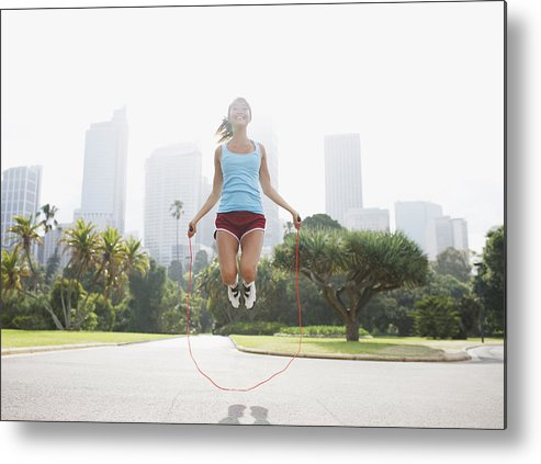 People Metal Print featuring the photograph Woman skipping rope in park by Tom Merton