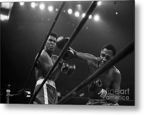 Joe Frazier Metal Print featuring the photograph Joe Frazier Punches Muhammad Ali by Bettmann