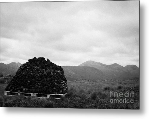 Ireland Metal Print featuring the photograph mound of Turf peat cut in a peat bog in front of mountains in Connemara County Galway by Joe Fox
