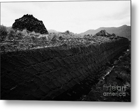 Ireland Metal Print featuring the photograph mound of Turf peat cut next to the cut seam in a peat bog in Connemara by Joe Fox