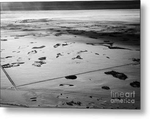 Aerial Metal Print featuring the photograph aerial view of snow covered prairies and remote isolated farmland in Saskatchewan Canada by Joe Fox