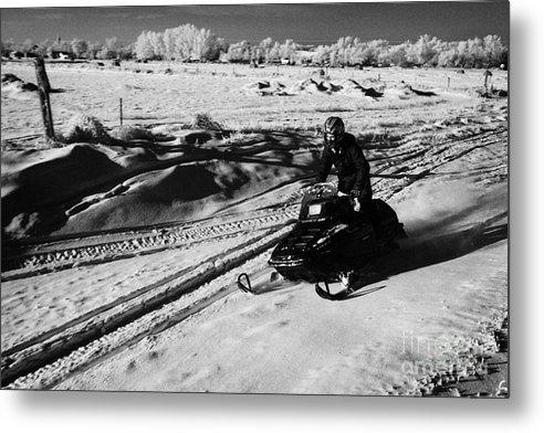 Man Metal Print featuring the photograph man on snowmobile crossing frozen fields in rural Forget Saskatchewan Canada by Joe Fox