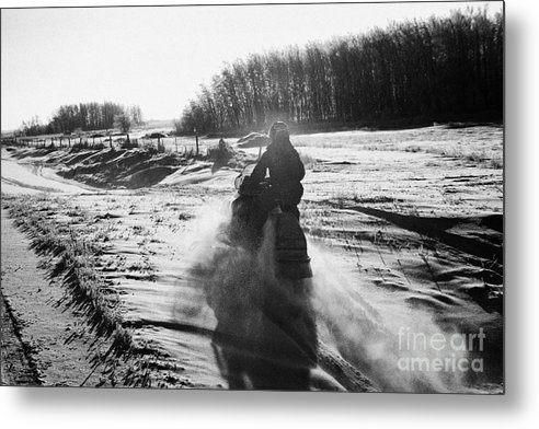 Man Metal Print featuring the photograph man on snowmobile crossing frozen fields in rural Forget Saskatchewan Canada by Joe Fox