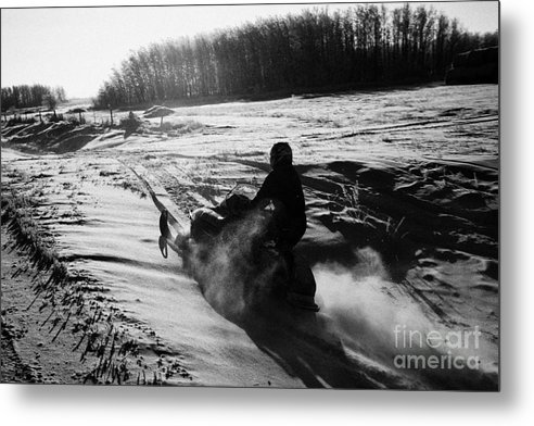 Man Metal Print featuring the photograph man on snowmobile crossing frozen fields in rural Forget canada by Joe Fox