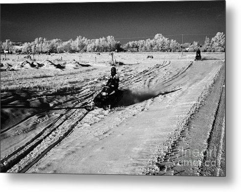 Man Metal Print featuring the photograph two men on snowmobiles crossing frozen fields in rural Forget Saskatchewan Canada by Joe Fox