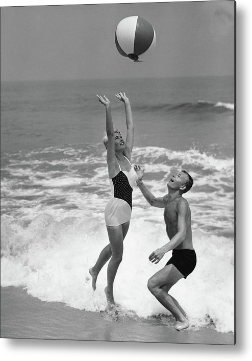 Young Men Metal Print featuring the photograph Young Couple Playing With Beach Ball At by Stockbyte