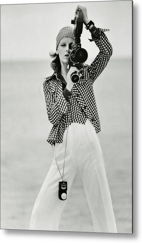 Fashion Metal Print featuring the photograph A Model Looking Through A Beaulieu Camera Wearing by Gianni Penati