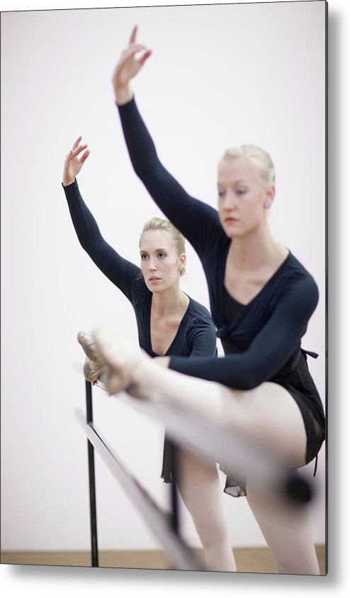 Ballet Dancer Metal Print featuring the photograph Female Ballerinas Stretching At The by Zero Creatives