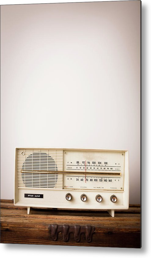 Desaturated Metal Print featuring the photograph Vintage Beige Radio Sitting On Wood by Ideabug