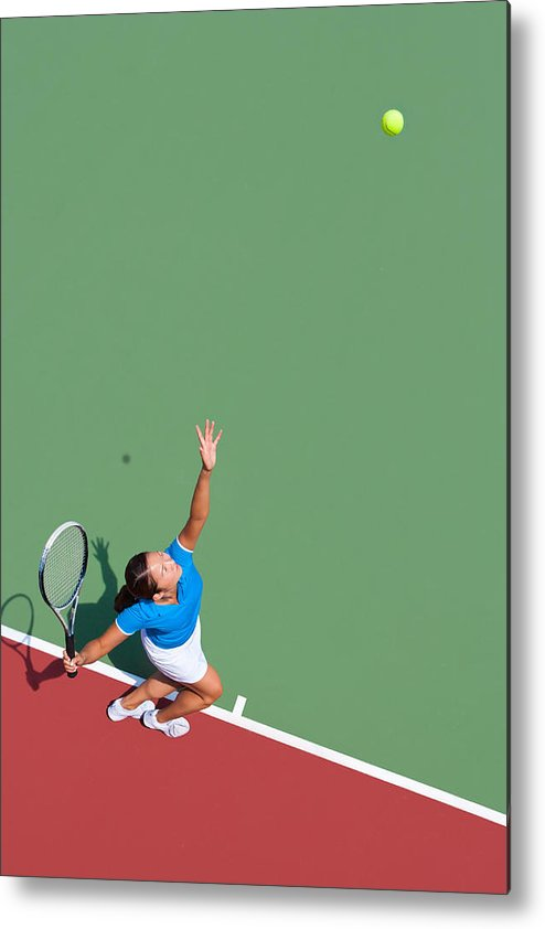 Asian And Indian Ethnicities Metal Print featuring the photograph Young tennis player serving by Nycshooter