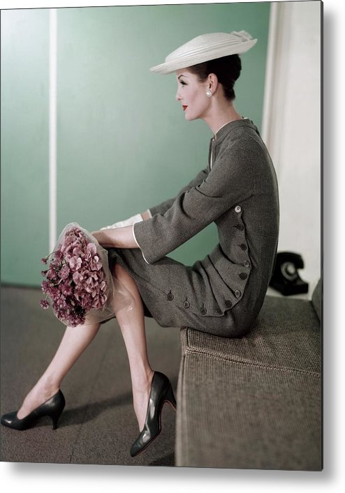 Fashion Metal Print featuring the photograph A Model Sitting Down With A Bouquet Of Flowers by Karen Radkai