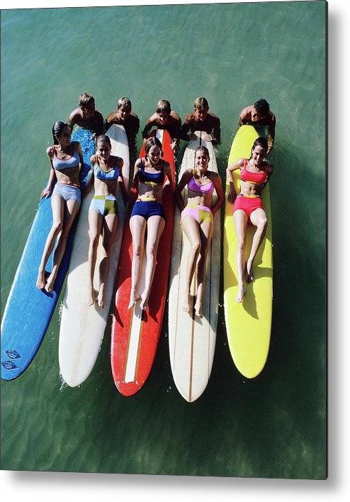 Fashion Metal Print featuring the photograph Models Wearing Bikinis Lying On Surfboards by William Connors